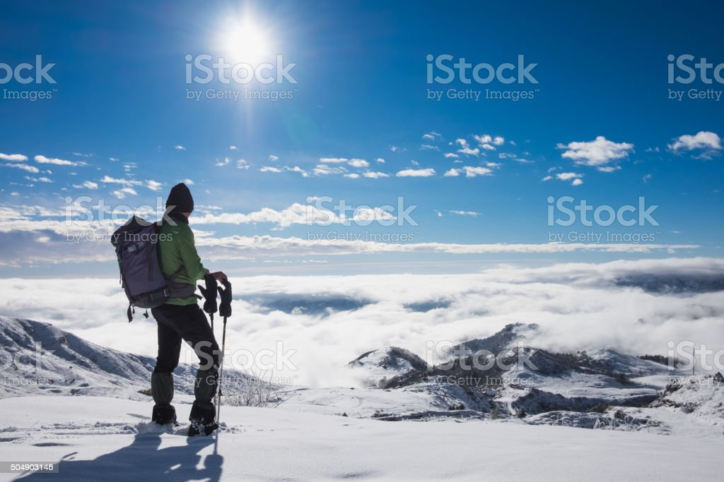 Alpinist on top of snowy mountain stock photo
