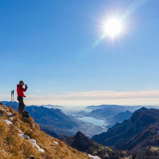 bergbeklimmer nemen van een pauze op de bergtop - lecco lombardije stockfoto's en -beelden