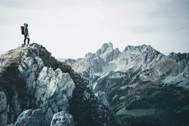 Alpinist Frau in warmen outdoor Sportbekleidung steht allein hoch oben in den österreichischen Bergen – Foto