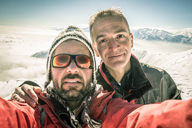 Alpinists selfie on the top Adult european men taking selfie on the mountain summit with snowcapped italian Alps in background. Concept of friendship and sharing achievments. Backlight, toned image, old retro touch, desaturated. desaturated stock pictures, royalty-free photos & images