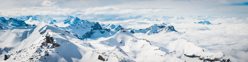 High altitude panoramic view across the crisp white glaciers, snow capped summits and dramatic rocky ridges of the Alps high in the idyllic mountain wilderness of the Bernese Oberland and Valais, Switzerland.