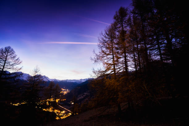 Alps forest at night with Oulx Panorama stock photo