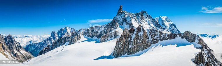 High altitude panoramic view above the clouds across the bright white glaciers, dramatic rocky pinnacles and high altitude summits of the Mont Blanc Massif and the Vallee Blanche from the Pointe Helbronner in Italy past the iconic Alpine peaks of the Aiguille du Midi to the Aiguille Verte and Les Drus, and down the Glacier du Geant down to the Chamonix valley in France. ProPhoto RGB profile for maximum color fidelity and gamut.
