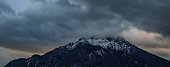 Alps lonely mountains snow peak dramatic moody landscape scenic view twilight winter time cloudy sky background