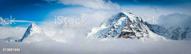 Photo of Alps mountain peaks above clouds Eiger and Jungfrau panorama Switzerland