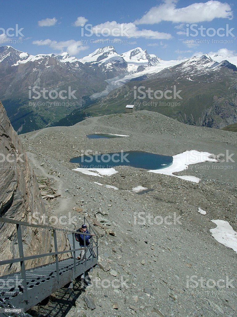 Alps, woman walking in the mountains on walkway royalty-free stock photo