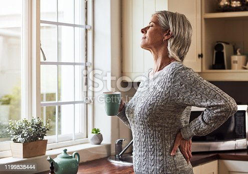 Cropped shot of a relaxed senior woman preparing a cup of tea with CBD oil inside of it at home during the day