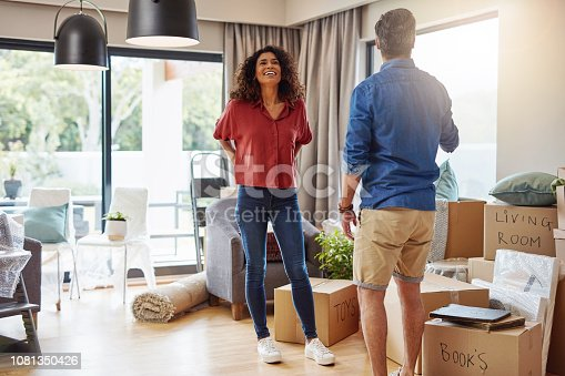 Shot of a cheerful young couple standing inside of their new home and getting ready to unpack boxes on moving day