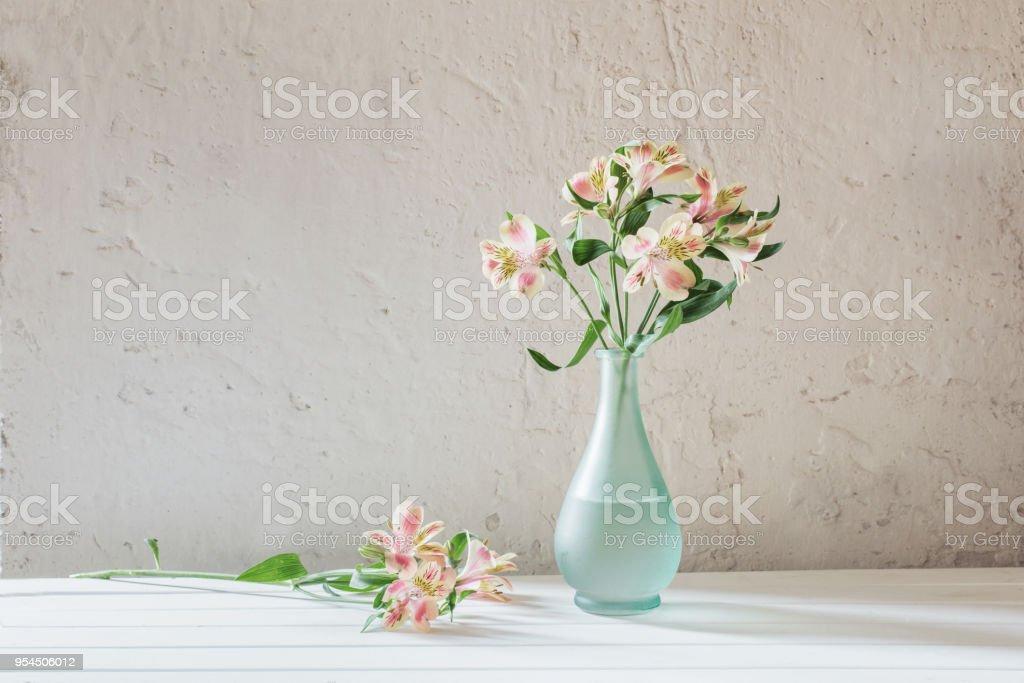 Alstroemeria in vase on grunge white background stock photo
