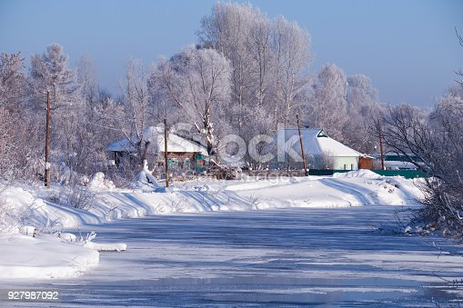istock Altai russian country village Talitsa under winter snow on bank of river 927987092
