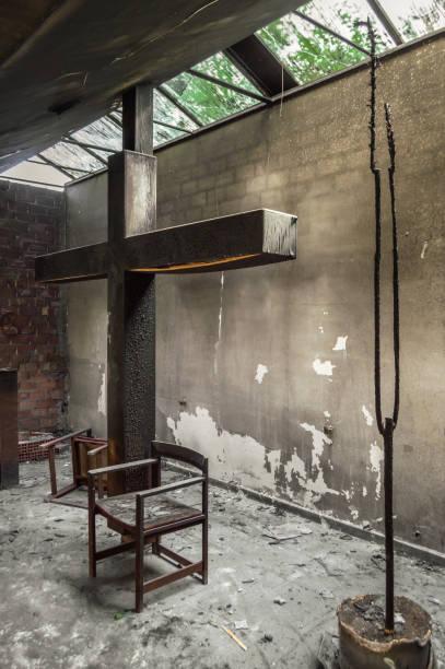altaret och enormt kors i en kyrka eller kapell som förstördes i en brand i ett ljus. resterna av brända religiösa plats med solljus passerar genom fönstren. - brand sotiga fönster bildbanksfoton och bilder