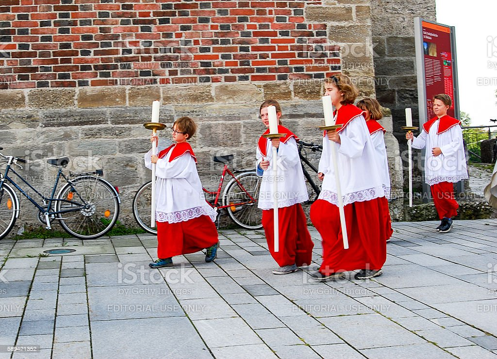 Altar boys leave church on day of Mary's Asumption stock photo