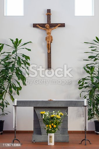 The Altar of a catholic church, in a clean design with some green plants and a bouquet of yellow flowers in front of the altar table. There is a wooden crucifix on the wall.