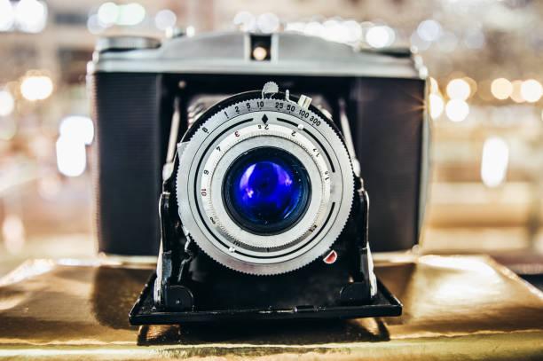alte retro-kamera mit blauer linse und faltenbalg - fuji sofortbildkamera stock-fotos und bilder