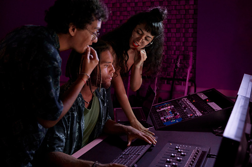Alternative band producing new album with african-american male music producer in professional music studio