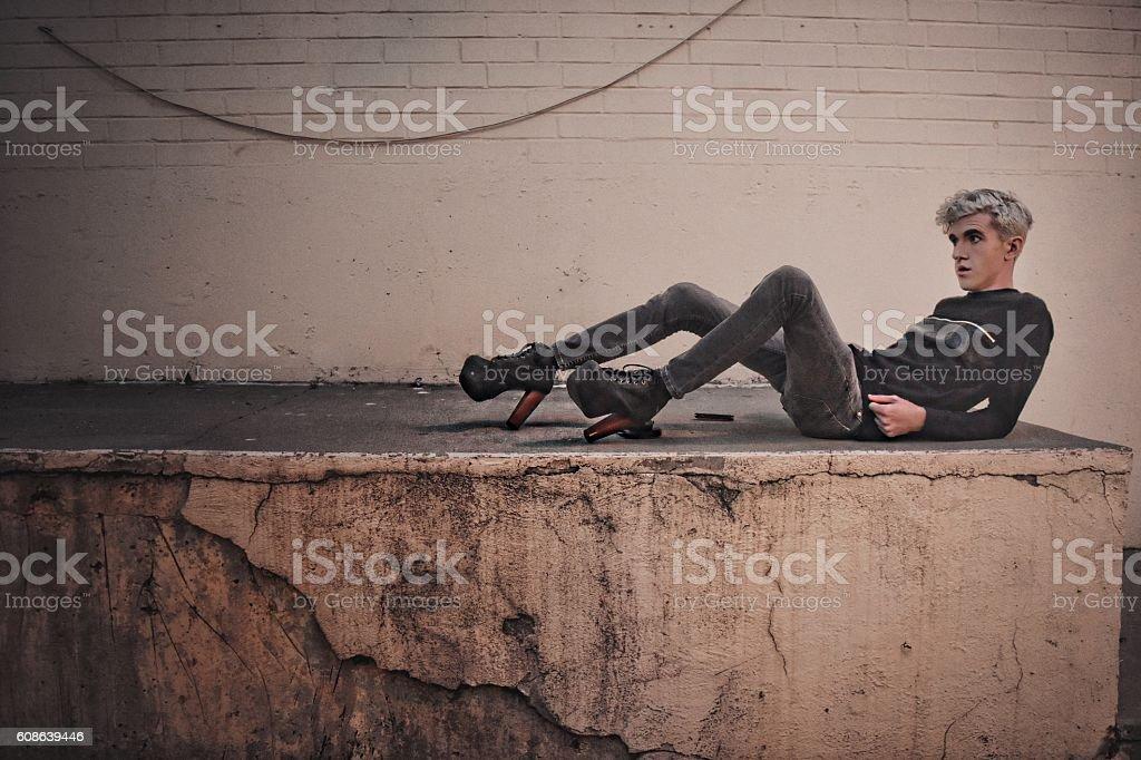 Alternative boy lounging on a concrete slab. stock photo