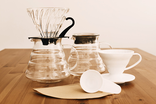 Alternative coffee brewing method. Stylish accessories and items for alternative coffee on wooden table. Glass flask with dropper, paper filters, glass and ceramic dripper for pour-over coffee