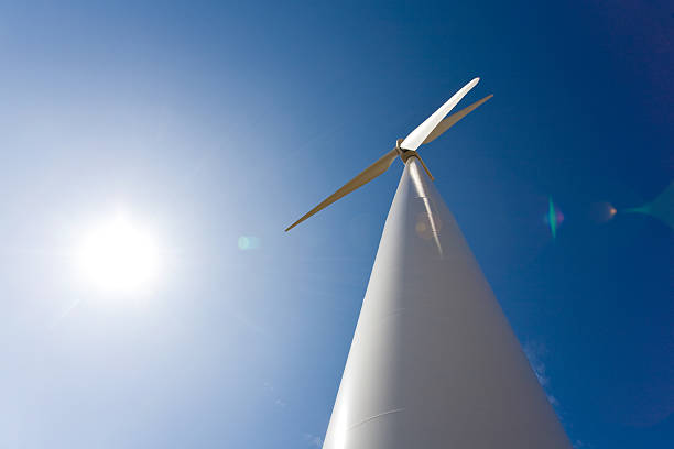 Alternative Energy, Wind & Solar Wide angle photo of a wind turbine and the sun creates a futuristic look and juxtaposes wind power with solar energy. Set against a deep blue sky with sun and clear skies. apothegm stock pictures, royalty-free photos & images
