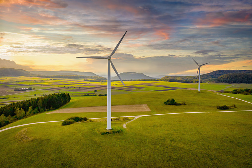 istock Alternative Energy Wind Turbine Green Landscape at Sunset 1200031421