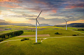 Aerial drone point of view of modern wind turbines in green rural landscape during a colorful sunset twilight. Green Energy, Alternative Energy Environment Concept Shot. Baden Württemberg, South Germany, Europe