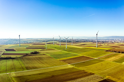Aerial view of wind turbines and agriculture field  in the early morning at sunrise.