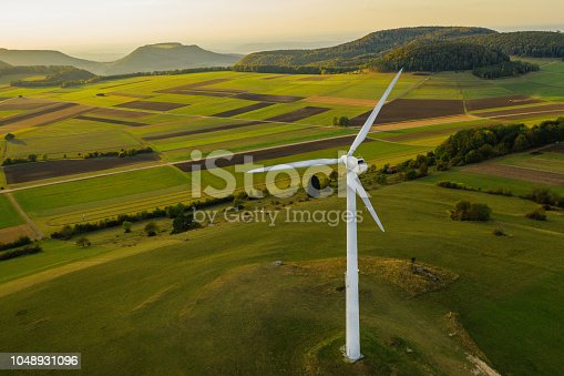 Aerial view of single wind turbine in green rural landscape at sunset. Green Energy, Alternative Energy Environment Concept Shot. Baden Württemberg, Germany.