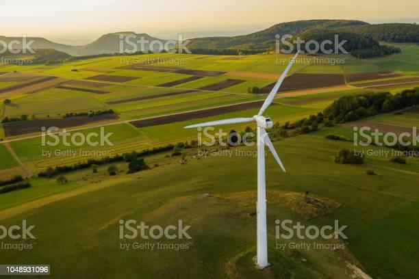 Alternative energy wind turbine in beautiful green landscape at picture id1048931096?b=1&k=6&m=1048931096&s=612x612&h=cl7pppmpqladfx 2gwws1jcpjwf9i5ln0rk2xlph3oo=