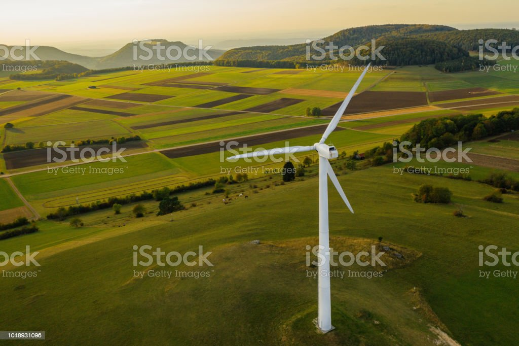 Alternative Energy Wind Turbine in Beautiful Green Landscape at Sunset stock photo