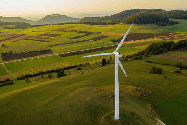 alternative energy wind turbine in beautiful green landscape at sunset - mulino a vento foto e immagini stock