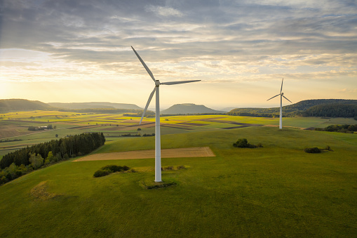 Wind Turbines in green rural landscape during sunset. Green Energy, Alternative Energy Environment Concept Shot. Drone Point of View. Baden Württemberg, Germany.