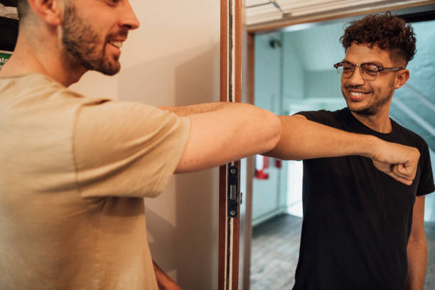Alternative Handshake Mixed race male using an elbow bump as an alternative handshake on his Caucasian male work colleague in the office. alternative pose stock pictures, royalty-free photos & images