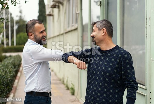 COVID-19 alternative handshake. Two people (male friends) bump elbows instead of hug or handshake. New ways of greeting that avoid handshakes and kissing are gaining popularity to stop the spread of the coronavirus