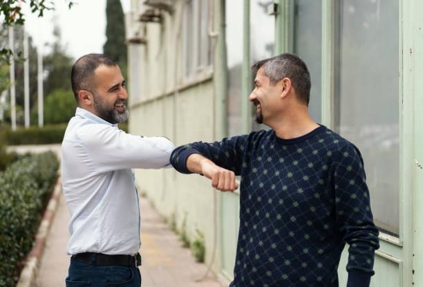 COVID-19 alternative handshake. Two people (male friends) bump elbows instead of hug or handshake. stock photo