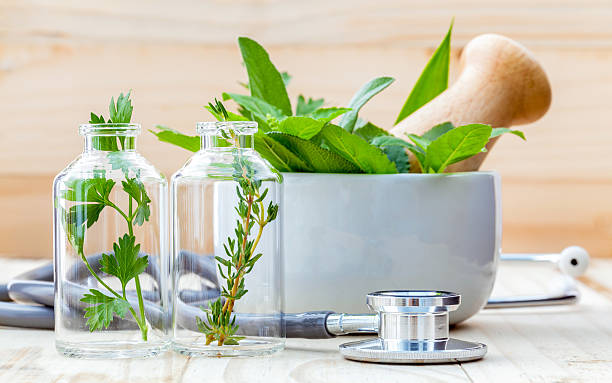 Alternative health care concept. Fresh herbs green mint ,rosemar Alternative health care concept. Fresh herbs green mint ,rosemary ,parsley ,sage and lemon thyme in laboratory glassware with stethoscope on wooden background. alternative medicine stock pictures, royalty-free photos & images