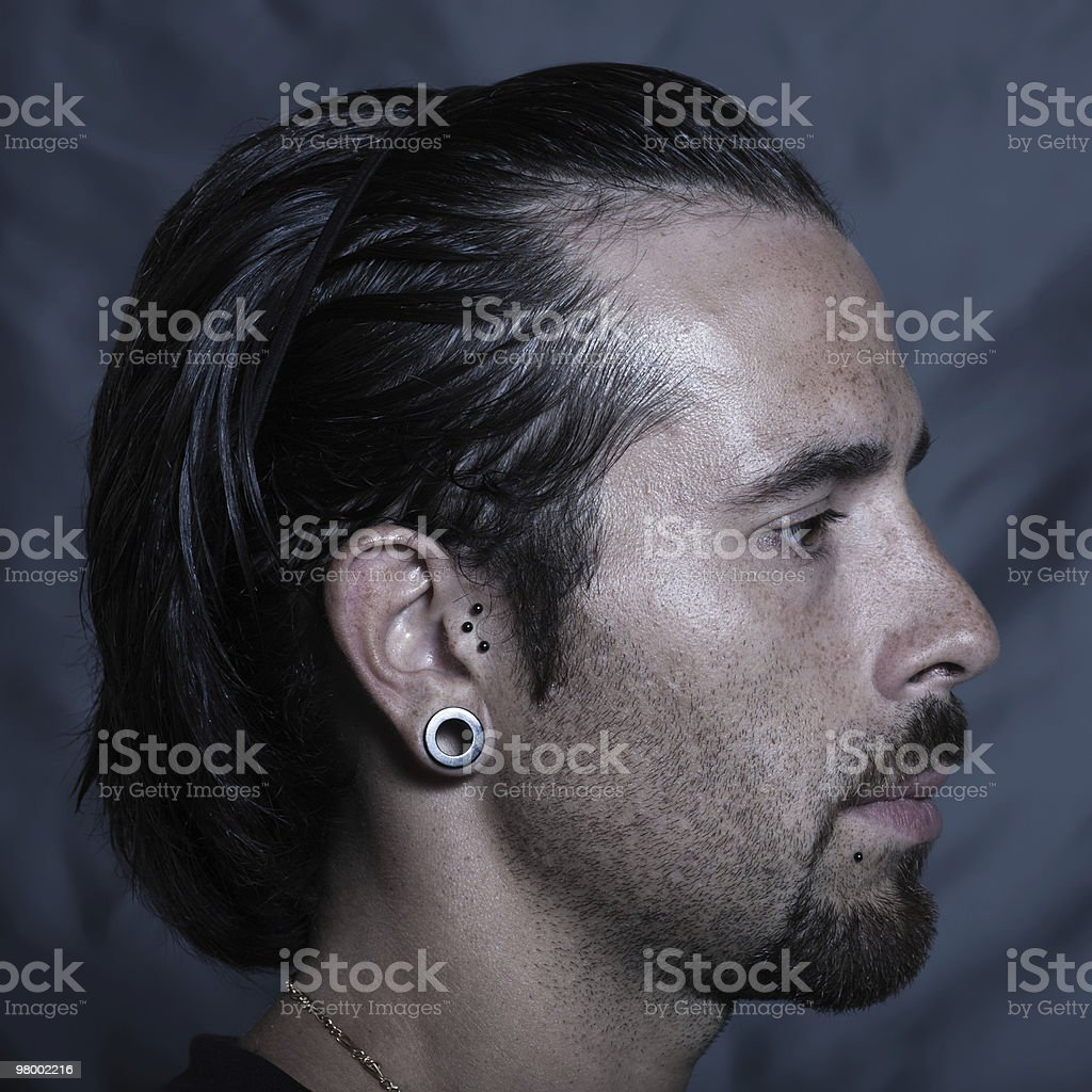 alternative lifestyle young man profile with piering and earings royalty free stockfoto