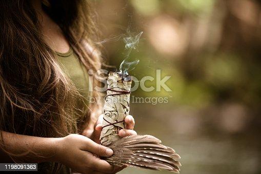 Young caucasian woman burning sage, practicing a purification ritual