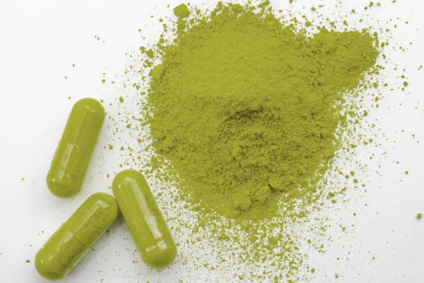 Medicina alternativa, manejo del dolor herbario y tratamiento de retiro opioide tema conceptual con una pila de polvo de kratom verde y cápsulas o píldoras aisladas sobre fondo blanco - foto de stock