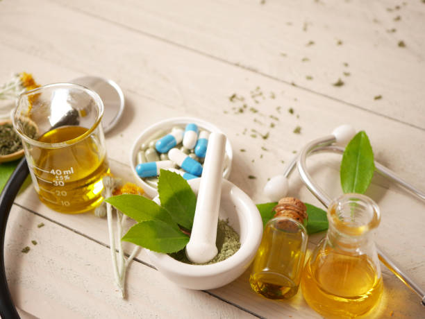 alternative medicine herbal treatment concept. herd with mortar or wooden table top view. capsule and solution medicine. stock photo