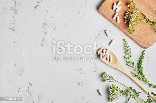 Herbal remedy in capsules and plants over grey background. Top view, flat lay with copy space