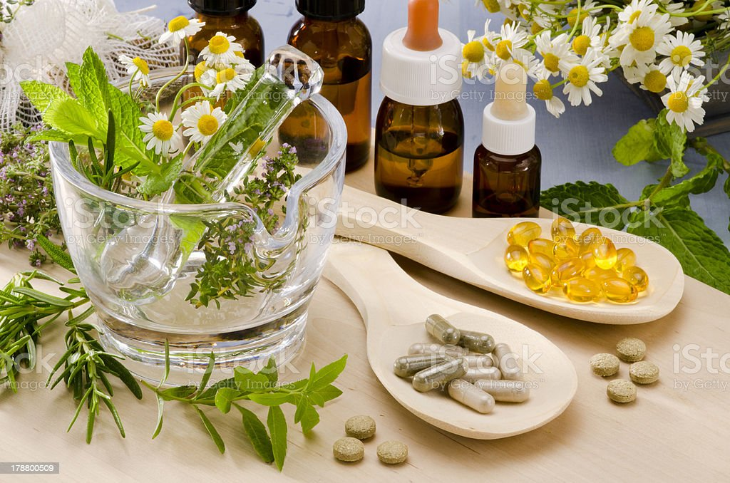 Alternative Medicine. Alternative Medicine. Rosemary, mint, chamomile, thyme in a glass mortar. Essential oils and herbal supplements. Alternative Medicine Stock Photo
