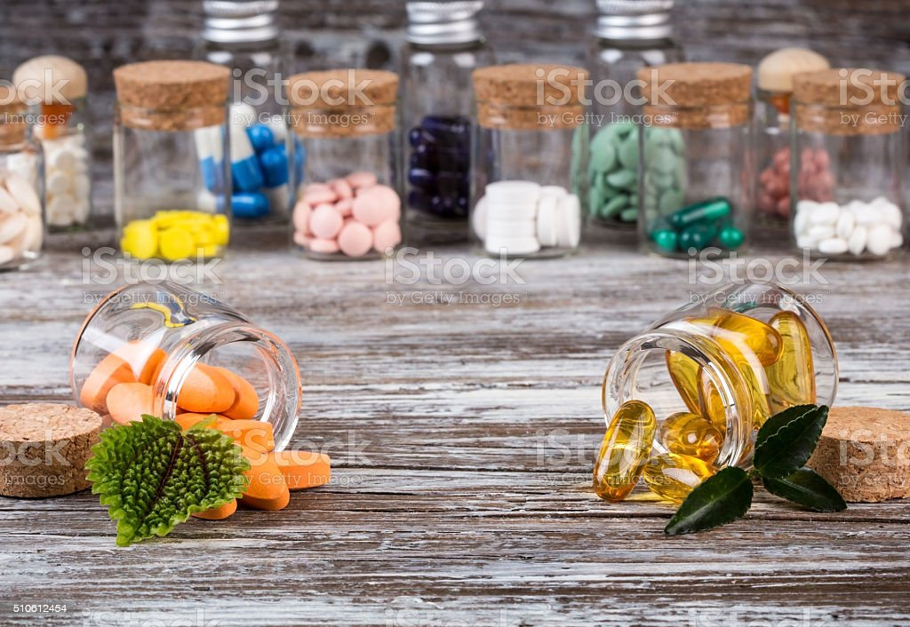 Alternative medicines with green leaves in glass containers stock photo