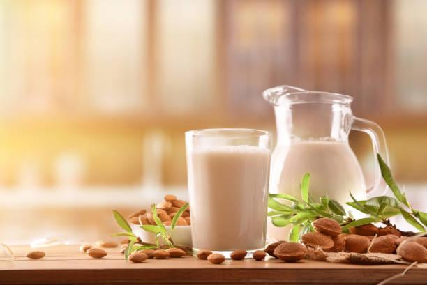 Alternativa leche de almendras en la mesa de madera en la cocina rústica - foto de stock