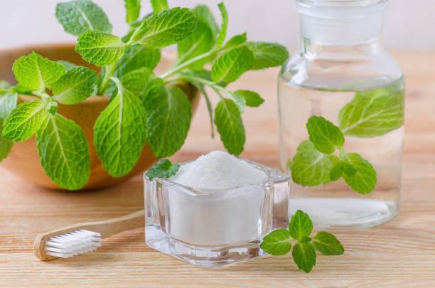 Alternative natürliche Mundwasser Flasche mit Zahnpasta Xylit, Natron, Salz und Holz Zahnbürste Closeup, Mint auf Holz – Foto