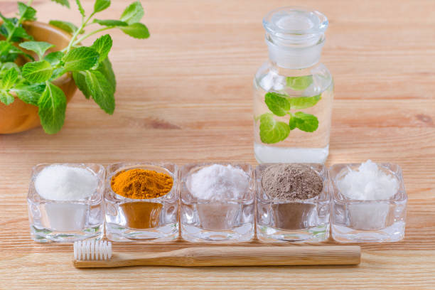 alternative natural mouthwash with mint, toothpaste xylitol or soda, turmeric - curcuma, himalayan salt, clay or ash, coconut oil and wood toothbrush, on wooden - sweeteners stock photos and pictures