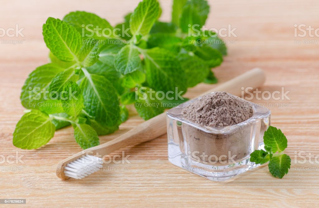 alternative natural toothpaste clay, ash and wood toothbrush, mint on wooden stock photo
