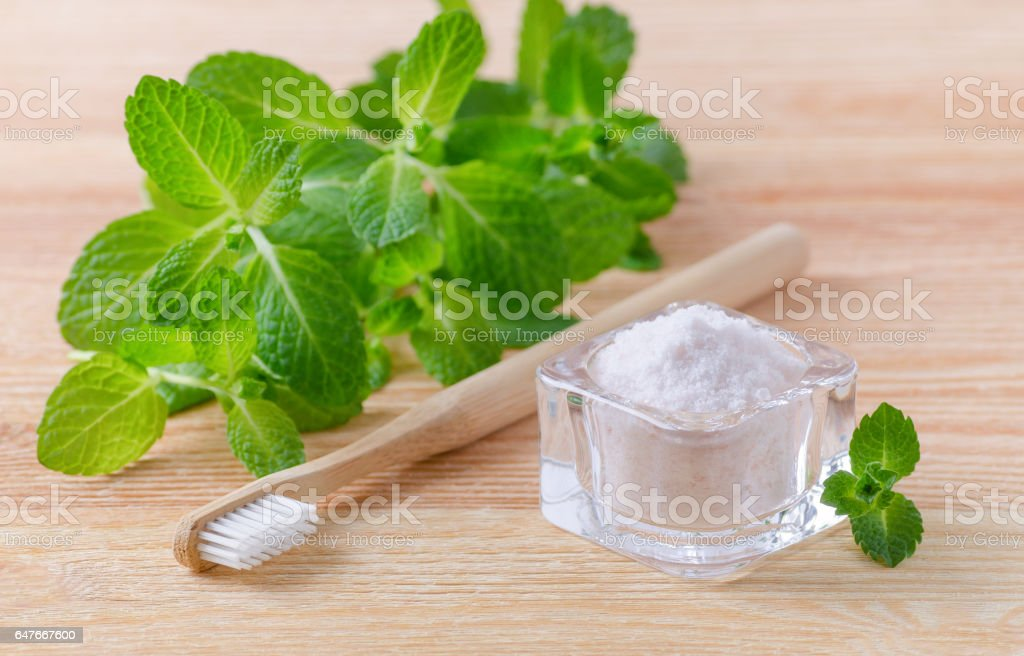 alternative natural toothpaste himalayan salt and wood toothbrush, mint on wooden stock photo
