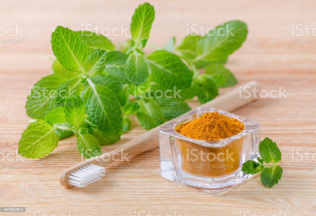 alternative natural toothpaste turmeric powder, curcuma and wood toothbrush, mint on wooden stock photo