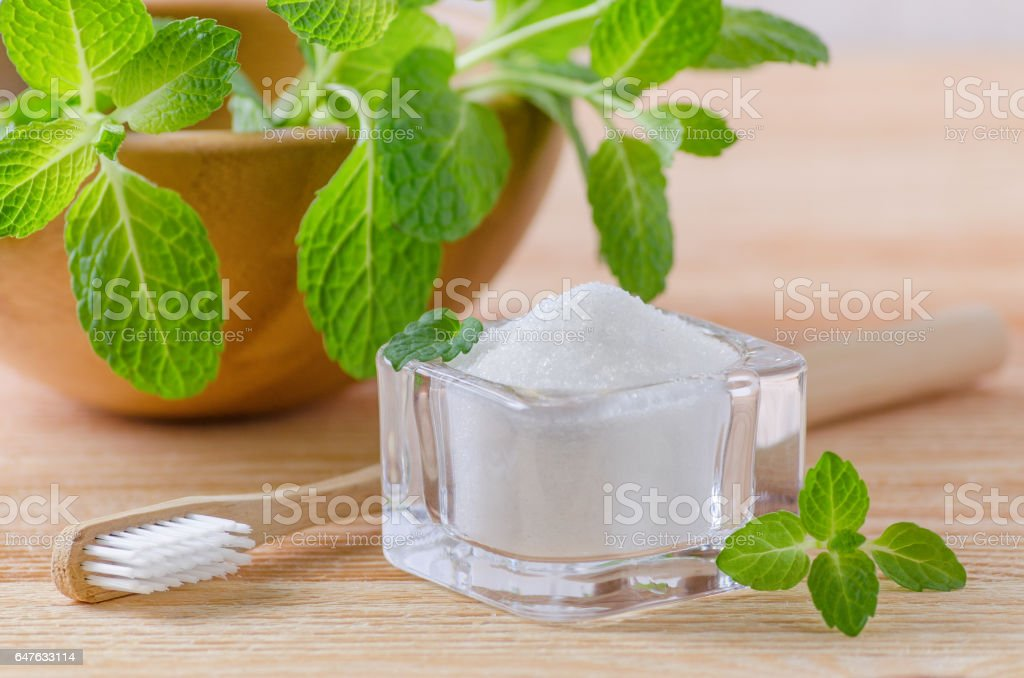alternative natural toothpaste xylitol, soda, salt, and wood toothbrush closeup, mint on wooden stock photo
