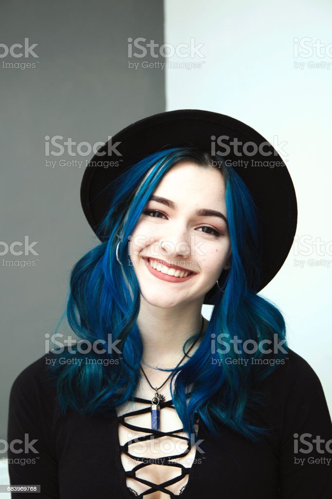 Alternative pretty teenager with blue hair and hat smiling - Photo