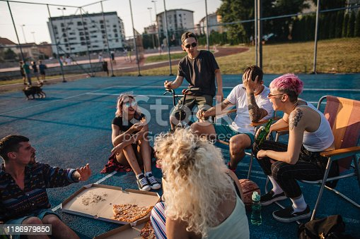 Friends sitting on a sports court drinking and eating fast food